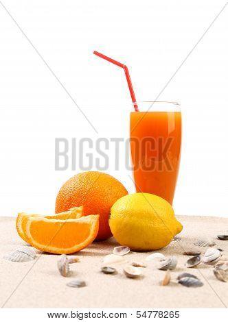 Juice, orange, lemon, shells on sand.
