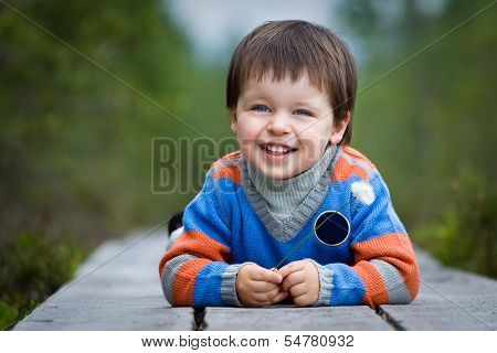 Admiring little boy laughing outdoors