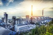 stock photo of silos  - Glow light of petrochemical industry on sunset - JPG