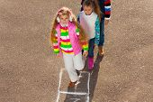 foto of hopscotch  - Group of kids playing outside with girl with long hair jumping on hopscotch - JPG