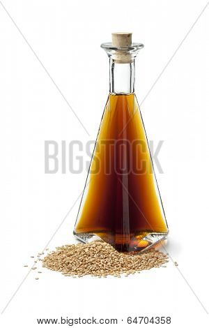 Sesame oil and roasted sesame seeds on white background