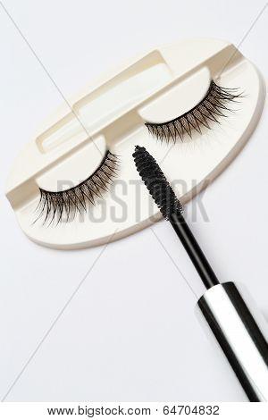 false eyelash set and mascara brush on grey background