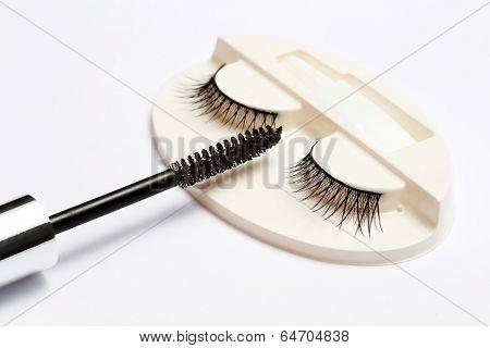 false eyelash set and mascara brush on white background