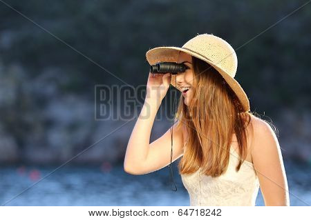 Happy Woman Looking Through A Binoculars On The Beach