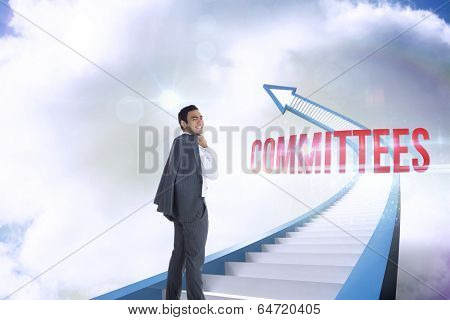 The word committees and smiling businessman standing against red staircase arrow pointing up against sky