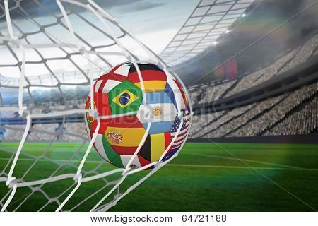 Football in multi national colours at back of net against large football stadium with lights