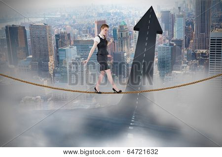 Businesswoman doing a balancing act against road turning into arrow