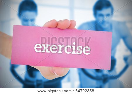 Woman holding pink card saying exercise against fitness class in gym