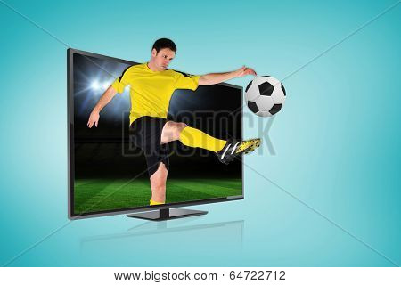 Composite image of football player kicking ball through tv against football pitch under spotlights
