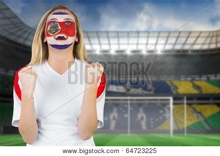 Excited costa rica fan in face paint cheering against football pitch in large stadium