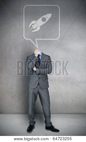 Composite image of headless businessman with rocket in speech bubble in grey room