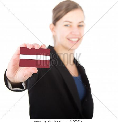 Business Woman Holding A Card With The Flag Of Latvia