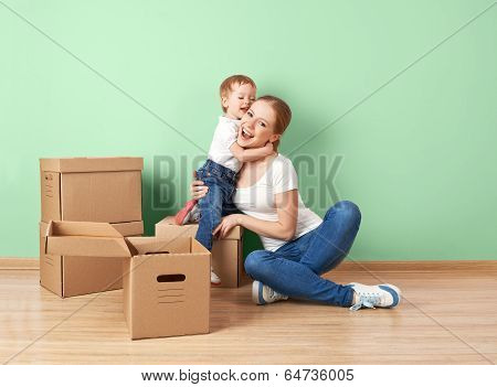 Happy Family Mother And Baby Daughter In An Empty Apartment With Cardboard Boxes