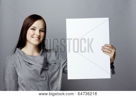 Portrait of a young smiling business woman with long brunette hair on gray studio background holding a blank white poster or an empty page with space for text