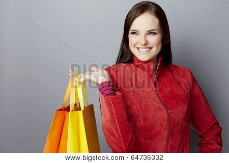 Portrait of a smiling young woman, with long brunette hair, on gray studio background, in luxury clothes, with bright shopping paper bags