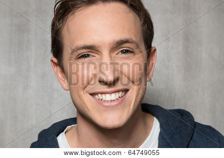 Portrait Of Young Man Laughing Against Background