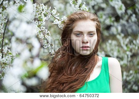 Portrait of Beautiful young woman standing near blooming trees in spring garden