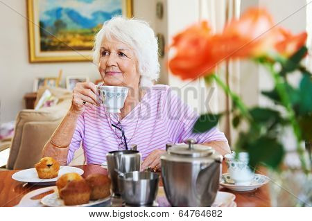 A content old lady enjoying some tea and a muffin