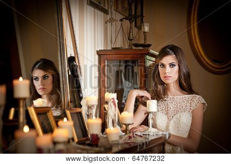 Beautiful sexy woman in white lace dress in vintage scenery with candles. Portrait of brunette