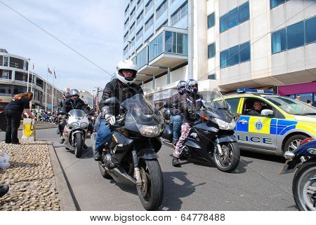 HASTINGS, ENGLAND - MAY 5, 2014: Motorcyclists ride along the seafront during the annual May Day biker rally. Started over 35 years ago, the event is now one of the largest bike gatherings in Britain.