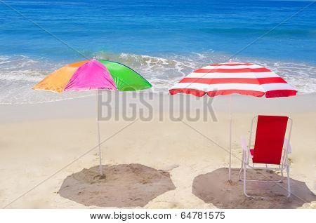 Beach Umbrellas And Chair By The Ocean