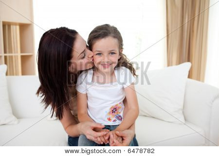 Attentive Mother Kissing Her Little Girl