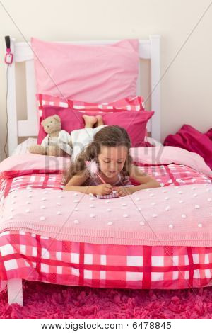 Little Girl Writing On Bed