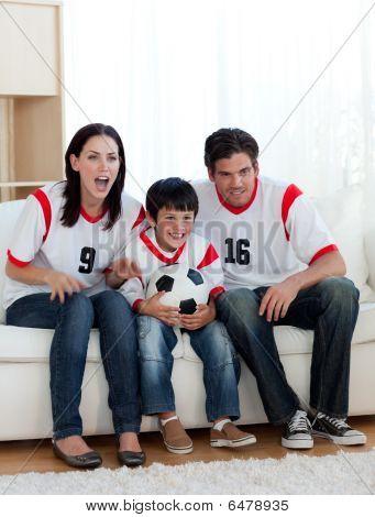 Os pais e o filho assistir um jogo de futebol