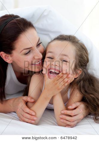Little Girl And Her Mother Having Fun On Bed