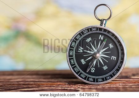Compass On The Table Against The Background Of A Tourist Card