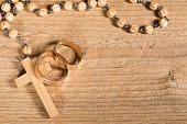 stock photo of rosary  - weding rings and rosary on the old wooden desk - JPG