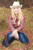 stock photo of cowgirl  - Smiling Cowgirl With Lasso Rope in Cattleshed - JPG