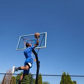stock photo of slam  - Young basketball player drives to the hoop for a high flying slam dunk - JPG