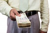 stock photo of gandhi  - An Indian business man holding out a stack of 500 rupee notes.