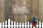 image of bird fence  - Blank rustic sign hanging over fence with red and blue birdhouse - JPG