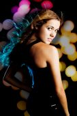 stock photo of party people  - Young fashion woman dancing on a night party with colorful light on the background - JPG