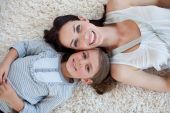 Happy Mother And Her Girl Lying On The Floor