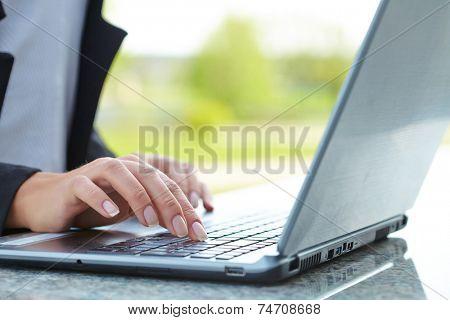 female hand writing on laptot