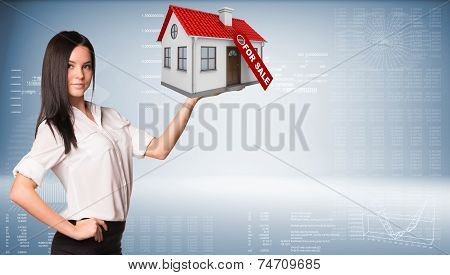 Businesswoman holding house in hand