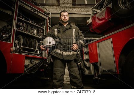 Cheerful firefighter near truck with equipment