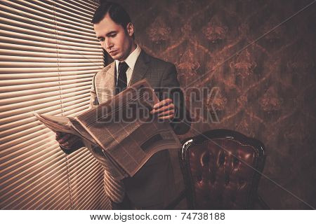 Man in suit reading newspaper near window