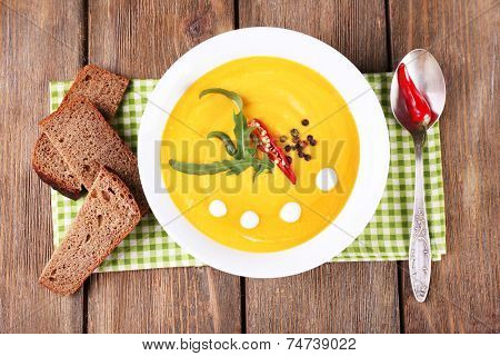 Pumpkin soup in white plate on napkin, on wooden background