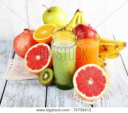 Fruit and vegetable juice and fresh fruits on napkin on wooden table on wooden wall background