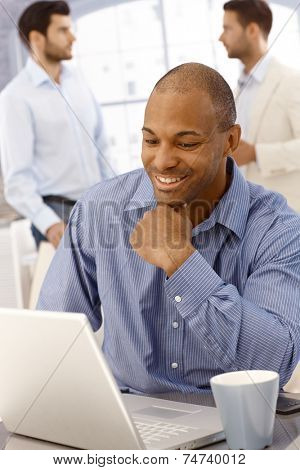 Closeup portrait of happy young afro-american businessman working with laptop computer, smiling.