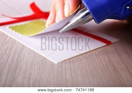 Woman's hand making postcard with red ribbon and bow with a help of glue gun