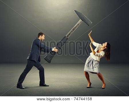 angry screaming man holding big hammer and hitting scared woman. photo in the dark room