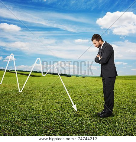 despondent businessman looking at negative graph at outdoor