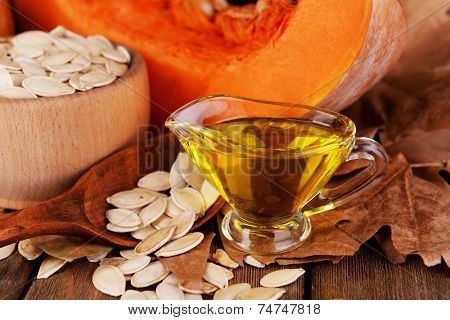 Pumpkin seed oil in glass sauce-boat and fresh pumpkin on wooden background