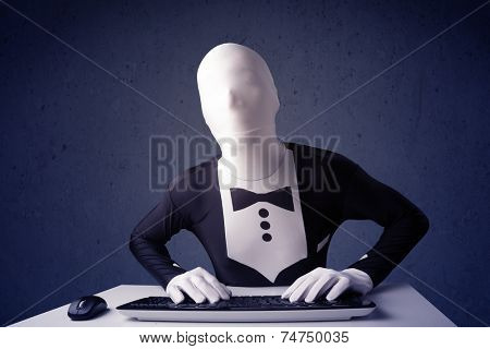 Man without identity working with keyboard and mouse on blue background