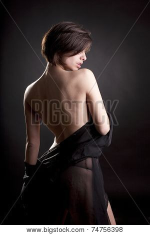 Sexy brunette woman wrapped with black tulle